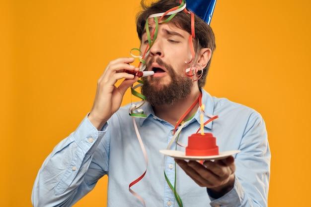 彼の頭のケーキの休日の誕生日にキャップと白いtシャツの感情的な男