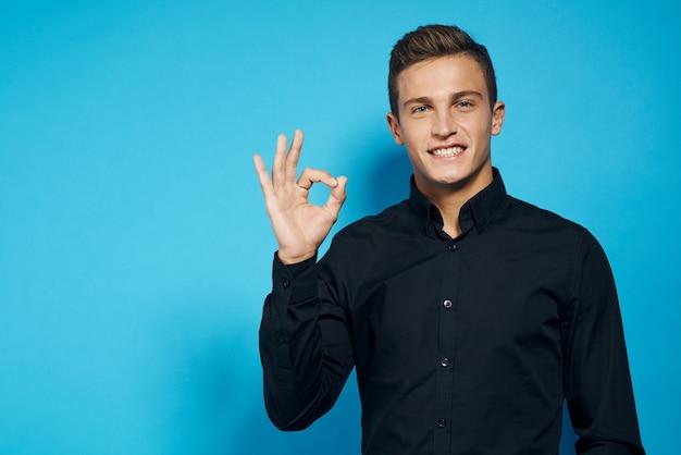 黒いシャツスタジオライフスタイル青い分離空間で感情的な男。