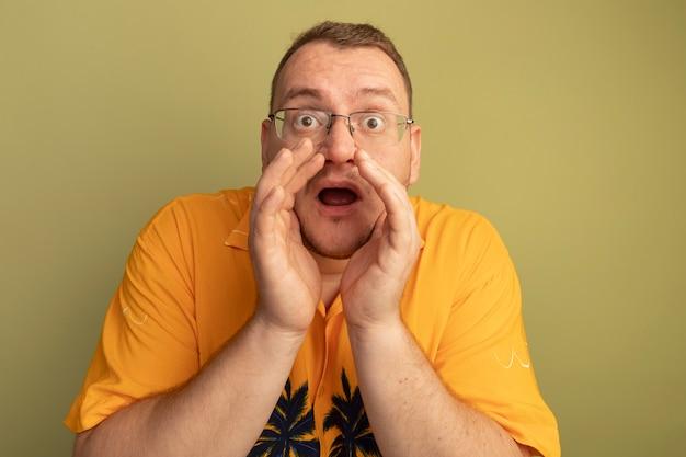 明るい壁の上に立っている口の近くの手で叫んでいるオレンジ色のシャツを着た眼鏡の感情的な男