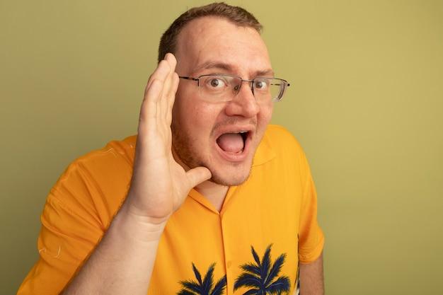 明るい壁の上に立って叫んで口に手を渡してオレンジ色のシャツを着て眼鏡をかけた感情的な男