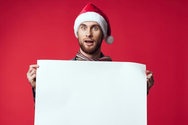 コピースペースの赤い背景を宣伝する新年の服の感情的な男