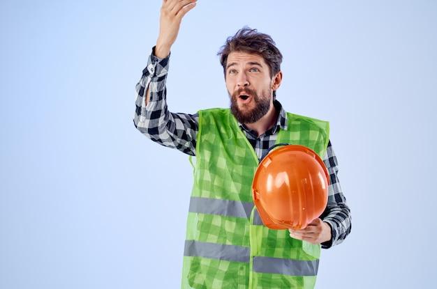 オレンジ色のヘルメット建設専門家の青い背景の感情的な男