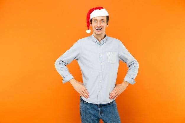 빨간 크리스마스 모자를 쓴 감정적인 남자가 벨트에 손을 대고 미소 짓고 카메라를 보고 있다