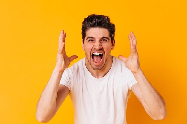 白いtシャツを着た感情的な男が猛烈に叫び、オレンジ色の空間でカメラをのぞき込みます。