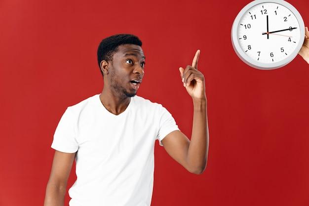Эмоциональный мужчина в белой футболке показывает на красном фоне часов