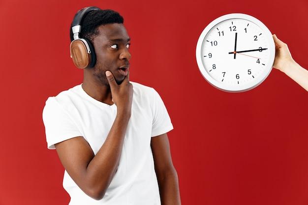헤드폰을 끼고 흰색 티셔츠를 입은 감정적인 남자는 시계 음악을 본다
