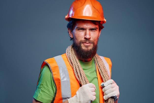 作業服の男の感情的なオレンジ色のヘルメットロープの専門家。高品質の写真
