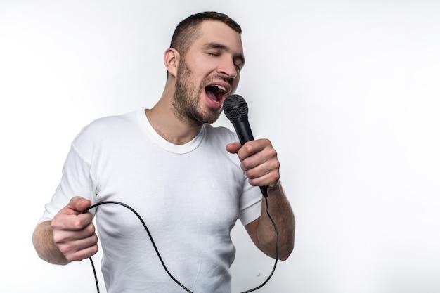감정적인 남자가 마이크에 노래를 부르고 흔들고 있습니다. 그는 그 일을 즐기고 있습니다. 흰색 배경에 고립