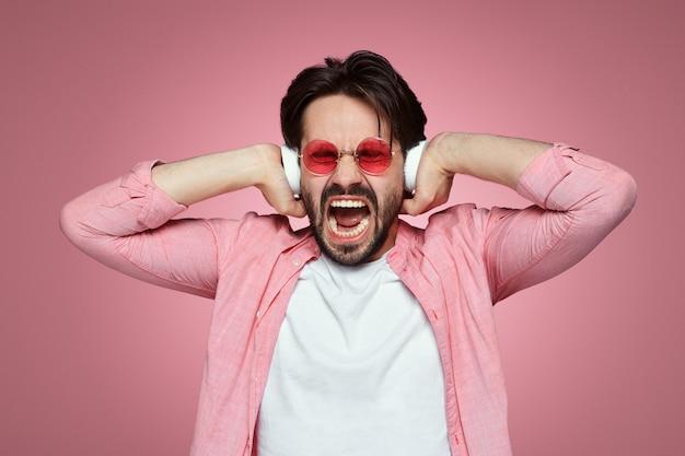 감정적 인 남자는 음악을 듣는 동안 헤드폰 비명에 손을 유지합니다.