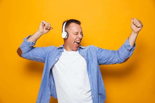Emotional man listening music with headphones.