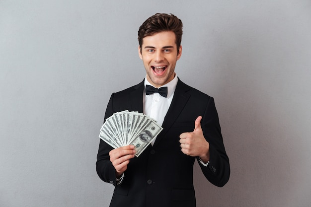 Emotional man in official suit holding money showing thumbs up.