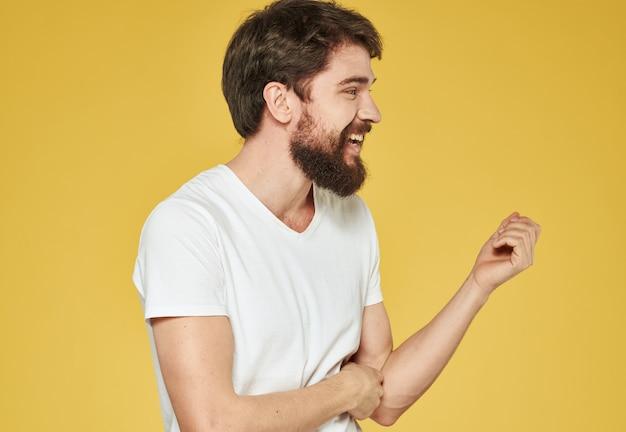 彼の手で身振りで示す黄色の背景の感情的な男は、楽しいトリミングされたビューです。高品質の写真