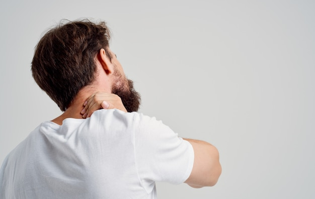 Emotional man pain in the neck health problems massage therapy light background