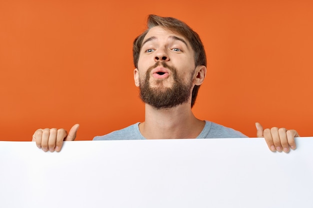 Emotional man peeking out from behind a poster on an orange background copy space mockup.