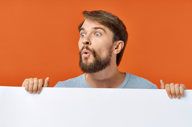Emotional man peeking out from behind a poster on an orange copy space mockup.