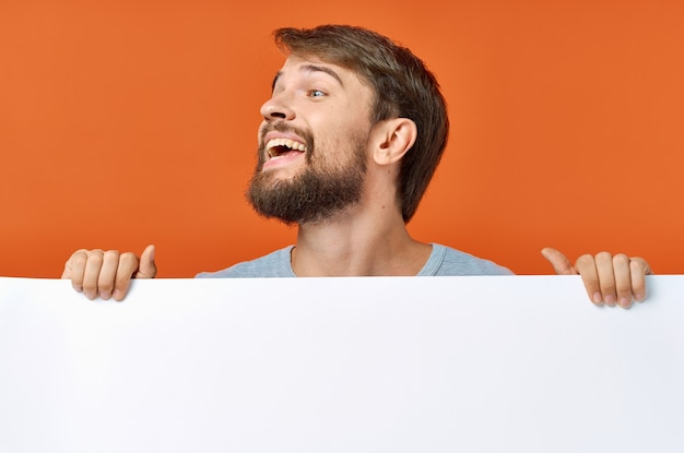 Emotional man peeking out from behind a poster on an orange mockup