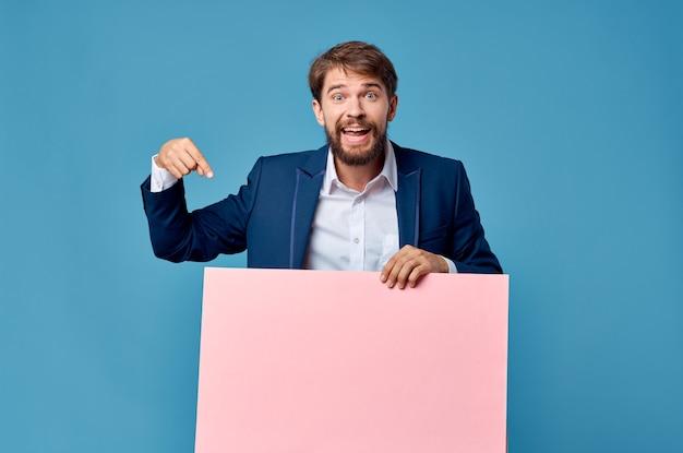 マーケティングの楽しいライフスタイルの青い背景の手に感情的な男のピンクの紙