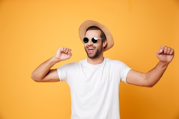 Emotional man in summer hat looking aside isolated dancing.