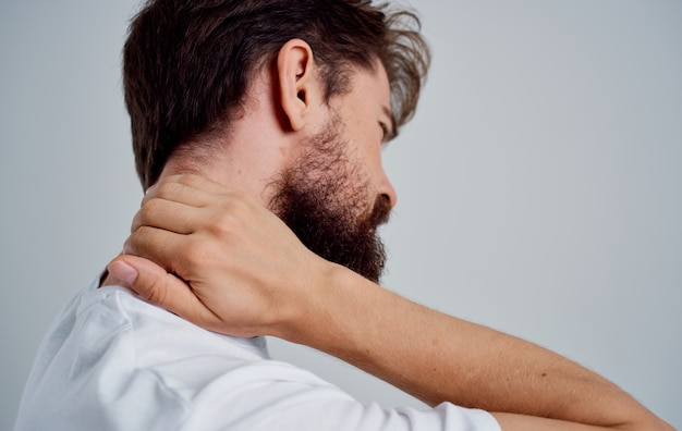 Emotional man in a white tshirt stress medicine pain in the neck studio treatment