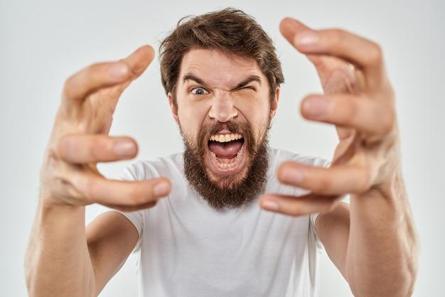 Эмоциональный мужчина с бородой, жестикулирующий руками крупным планом.
