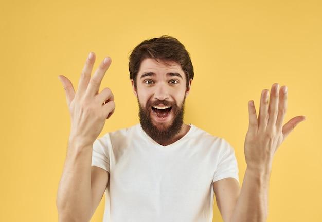 彼の手で白いtシャツのジェスチャーでひげを持つ感情的な男
