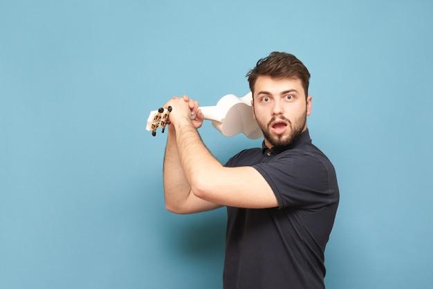 Эмоциональный мужчина с бородой машет укулеле в руке на синем в темной рубашке.