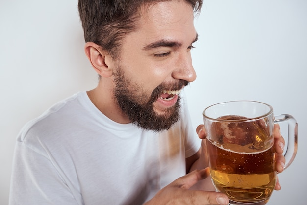 Эмоциональный мужчина с большой кружкой пивного алкогольного напитка, жестикулирующий красиво