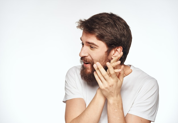 Emotional man with a beard holds his hands near his face on a light background cropped view