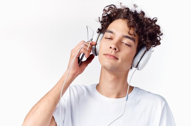 巻き毛とヘッドフォンで音楽の明るい背景を聞く感情的な男