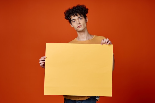 Emotional man with curly hair yellow poster in hands. high quality photo