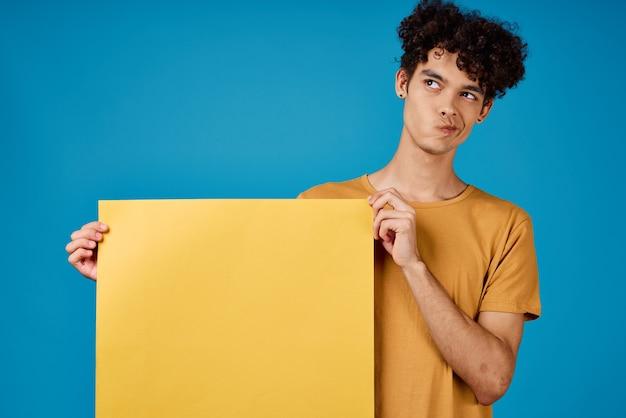 Эмоциональный мужчина с вьющимися волосами желтый плакат в руках копией пространства