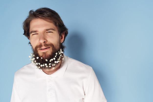 ひげの白いシャツの青い背景に花を持つ感情的な男。高品質の写真