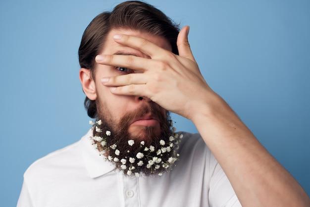 ひげの白いシャツの青い背景に花を持つ感情的な男