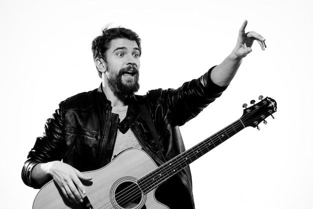 Эмоциональный мужчина с гитарой, музыкальная черная кожаная куртка, образ жизни, светлый фон