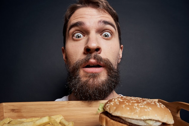 Эмоциональный мужчина с гамбургером и картофелем фри