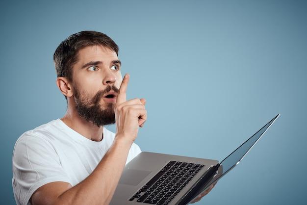 青い背景モニターキーボードインターネットモデルの手にラップトップを持つ感情的な男