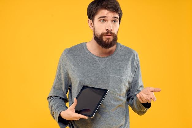 手にタブレットを持つ感情的な男。技術インターネットデバイスの概念