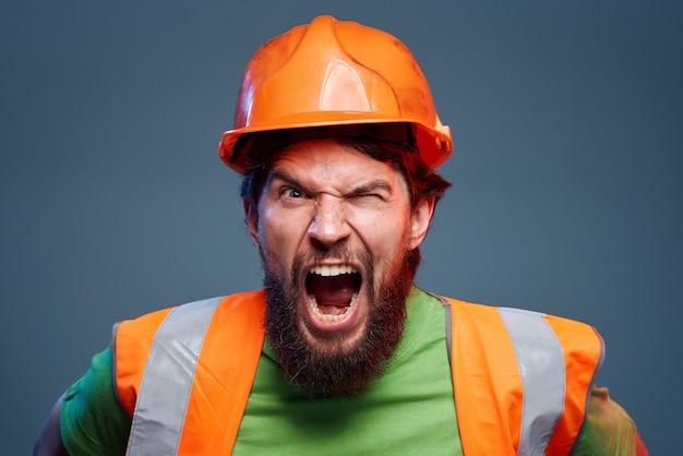 感情的な男性労働者オレンジペイントハードワーク。高品質の写真