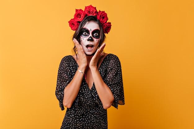 그녀의 머리에 꽃을 가진 감정적 인 멕시코 검은 머리 여자는 충격을받은 얼굴을 손으로 만지고 있습니다.