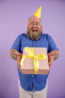 青いシャツと黄色い帽子を身に着けている感情的な中年の太った男は、スタジオで紫色の背景に立って、ギフトボックスで手に焦点を当てる