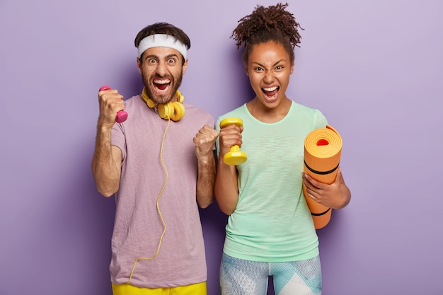 Emotional mixed race woman and man shout loudly, hold karemat and weights, have training with coach, yell from despair, being tired of workout, isolated on purple wall. people, sport, lifestyle