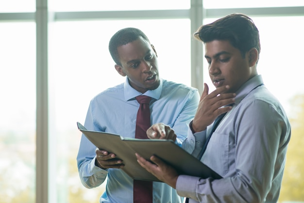 Emotional multi-ethnic coworkers discussing business document