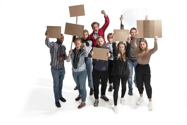 Эмоциональная мультикультурная группа людей, кричащих, держа в руках пустые плакаты на белом