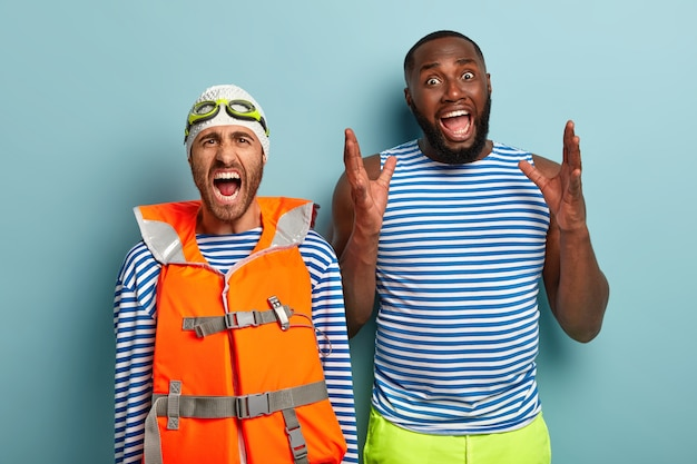 Emotional multiethnic two men shout loudly, express negative emotions, displeased with bad news, wear sailor vests, safety lifejacket