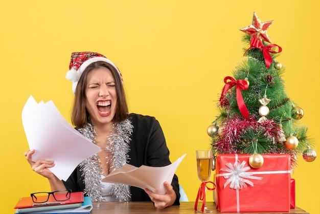 Emotiva donna d'affari nervosa in tuta con cappello di babbo natale e decorazioni di capodanno che tiene documenti e seduta a un tavolo con un albero di natale su di esso in ufficio