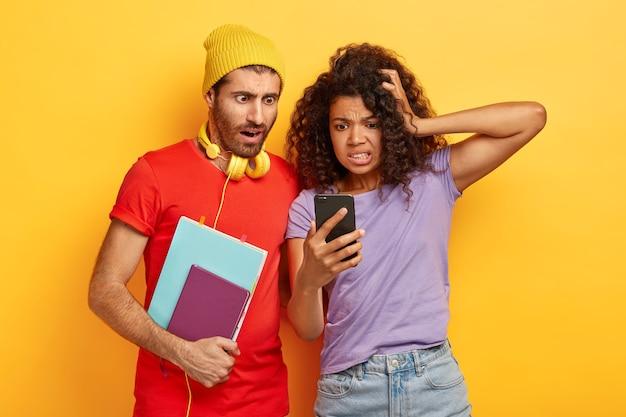 Studenti di razza mista nervosi emotivi leggono informazioni scioccanti dal sito web, fissano lo smartphone, portano il blocco note