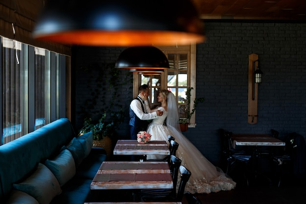 Emotional newlyweds hugging near the window. portrait of newlyweds in stylish room. wedding couple in a room with a stylish interior with lamps. wedding day