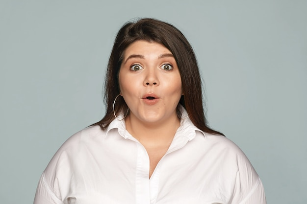 Emotional obese chubby young brunette female employee in formal shirt opening mouth expressing full disbelief, receiving unexpected raise in salary. human facial expressions, feelings and reaction