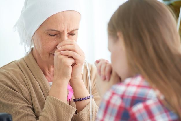 Эмоциональная молодая дочь белого кавказца с надеждой и улыбкой посещает и призывает поддержать ее мать, которая борется с больничной палатой рака груди, кампания по информированию о раке груди.