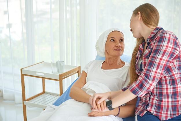 Эмоциональная молодая дочь, белая кавказская с надеждой и улыбкой, посещает и призывает поддержать свою мать, которая носит головной платок и борется с раком груди в чистой и чистой больничной палате